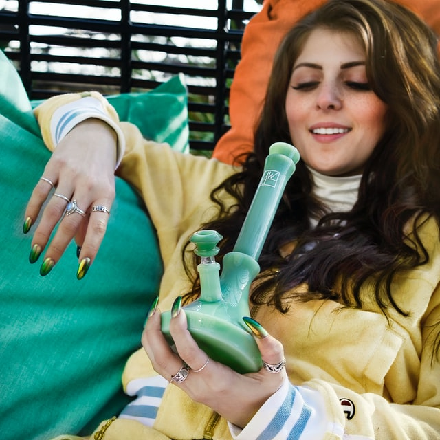 young woman smoking a bong on a lounger