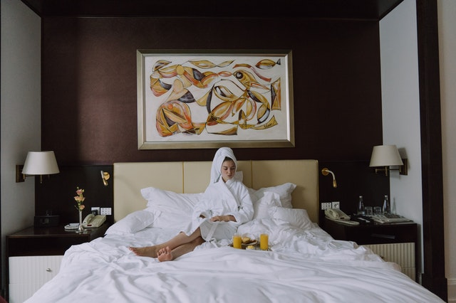 woman on a hotel bed Massachusetts Cannabis Tourism Guide